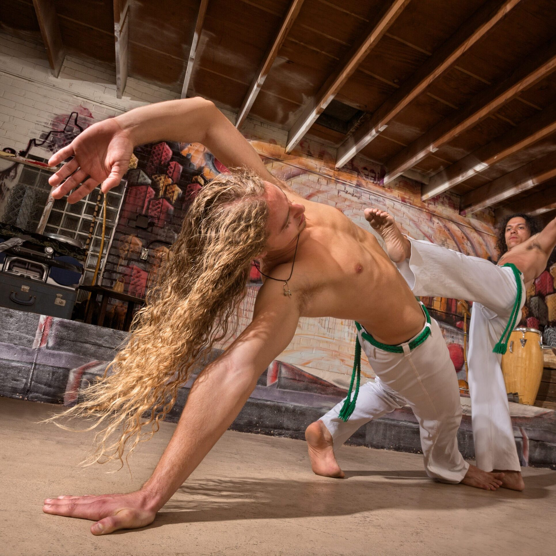 Young male capoeira partners performing kicks indoors