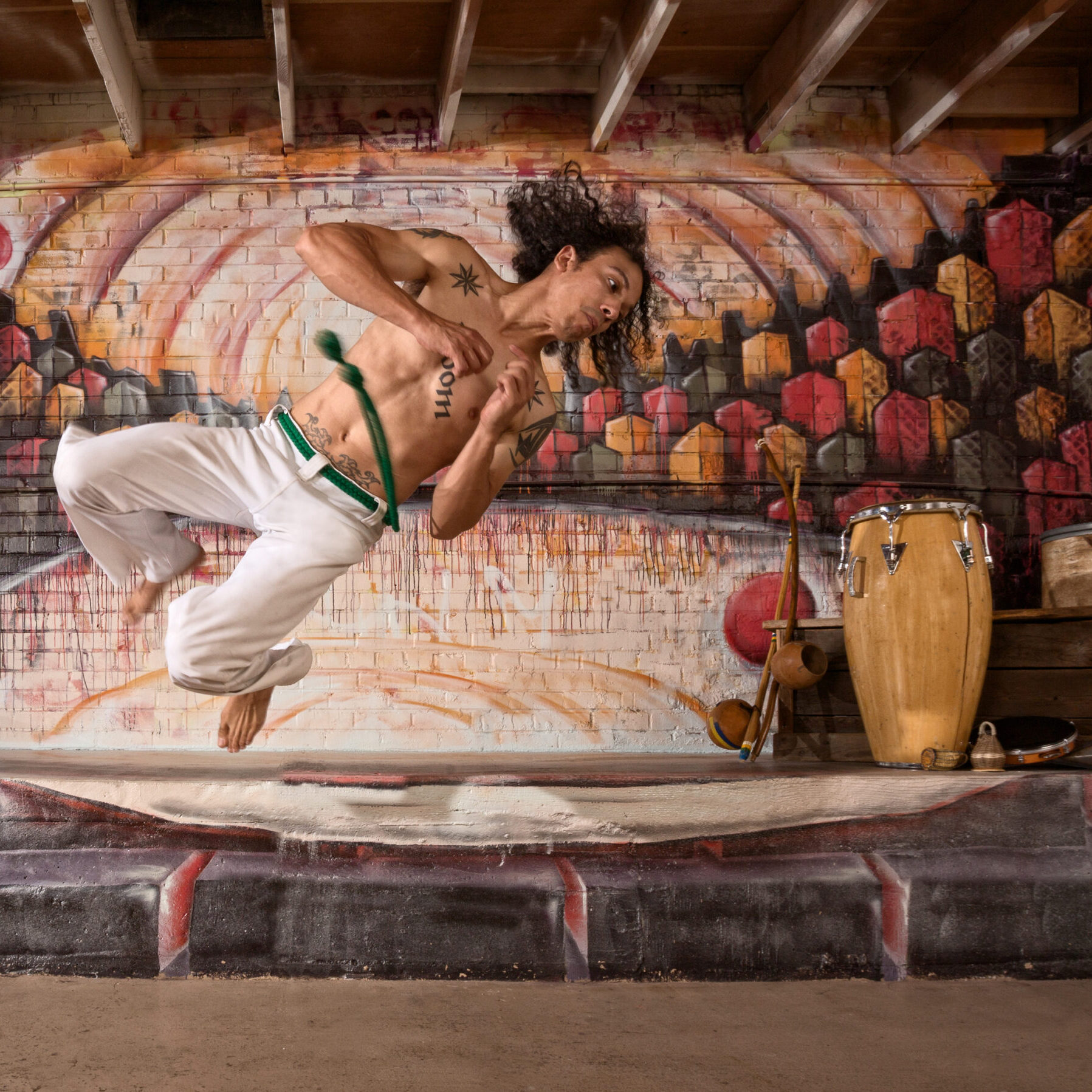 Handsome mixed capoeira performer flipping mid air