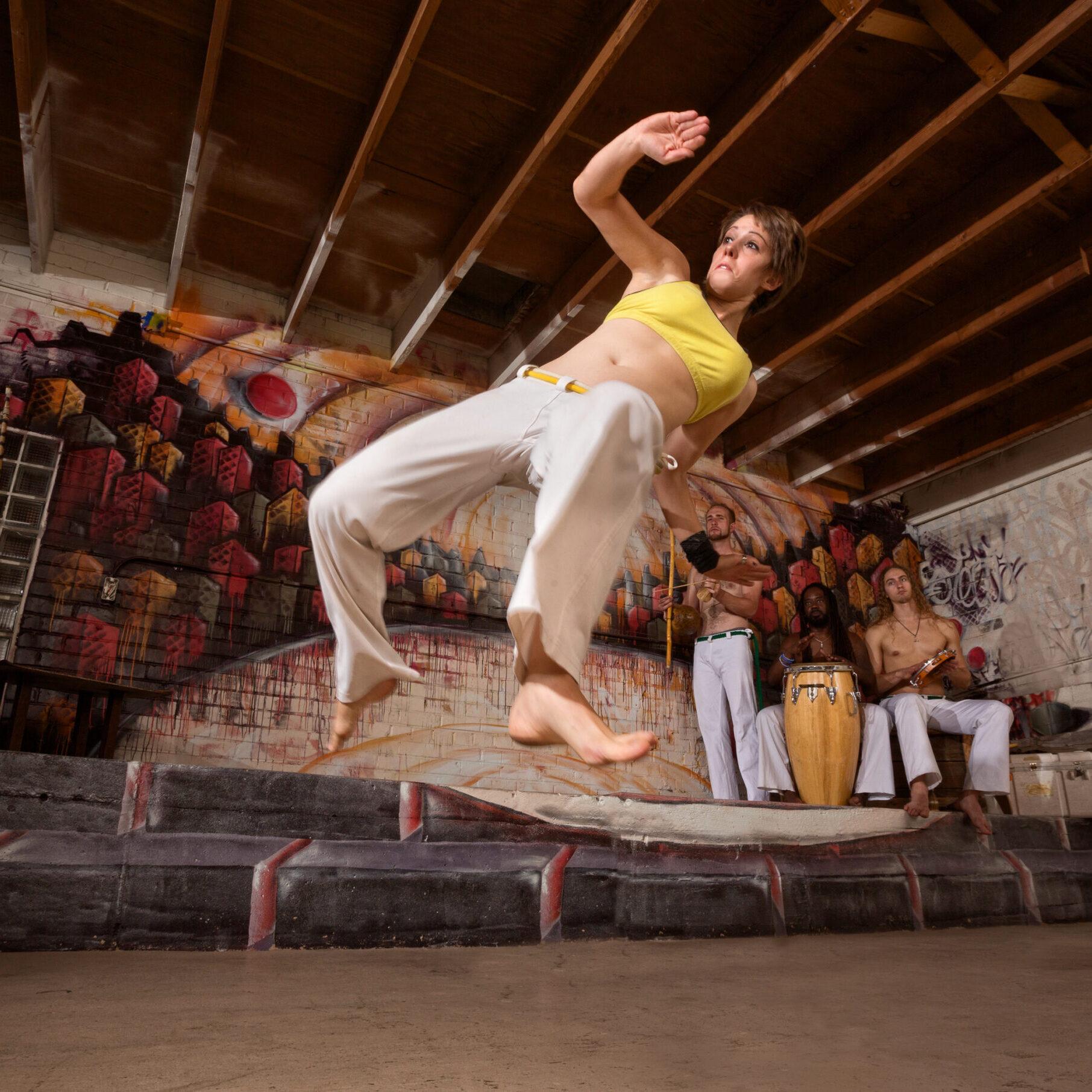 Flexible woman performing a capoeira jumping kick